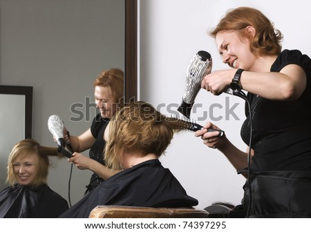 stylist drying woman hair in beauty salon - stock photo