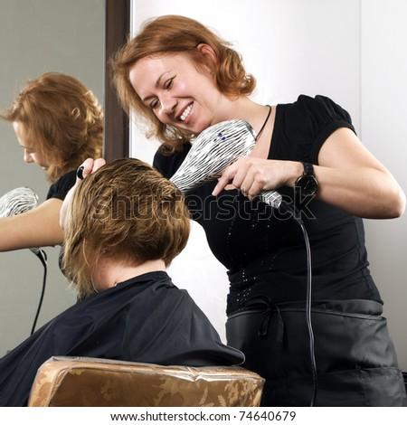 stylist drying woman hair in beauty salon - stock photo