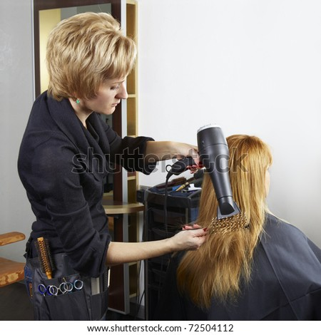 stylist drying woman hair in beauty salon. Space for text. - stock photo