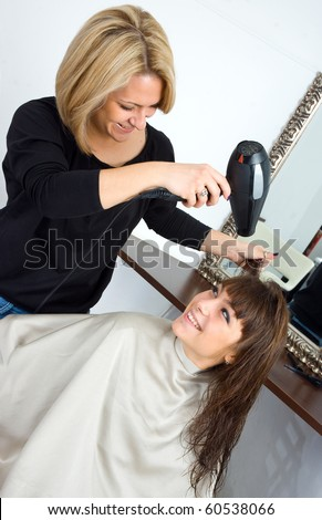 stylist drying woman hair in salon - stock photo