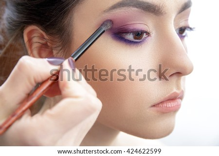 Stylist hand applying eye make-up to the eyelids of a young beautiful model.