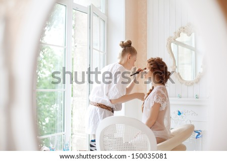 Stylist makes makeup bride on the wedding day - stock photo