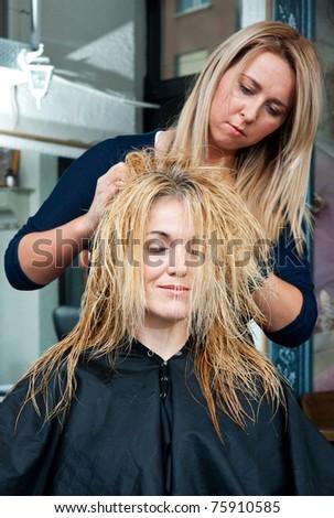 stylist massaging woman head in salon - stock photo