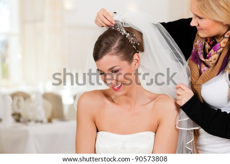 Stylist pinning up a bride's hairstyle and bridal veil before the wedding - stock photo