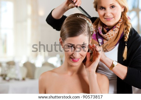 Stylist pinning up a bride's hairstyle before the wedding
