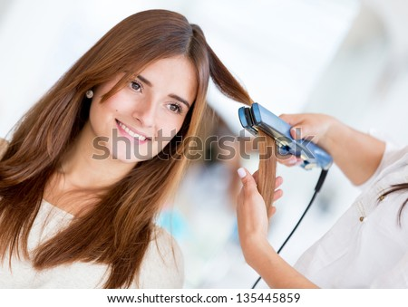Stylist using a hair straightener on a woman at the salon - stock photo