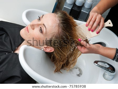 stylist washing and combing woman hair in hairsalon pool - stock photo
