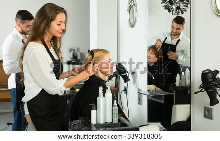 Stylists works with woman hair in salon - stock photo