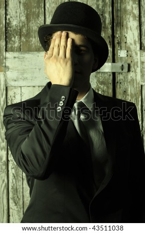 Stylized abstract portrait of a dapper man in top hat and suit covering half of his face with hand - photo has a slight green toned effect - stock photo