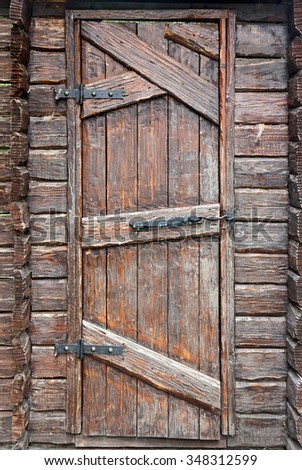 Stylized antique wooden door with wrought-iron hinges and hook