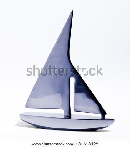 Stylized blue toy sailboat crafted of two pieces,one for the hull and one for the mast and sails, isolated on a white background - stock photo