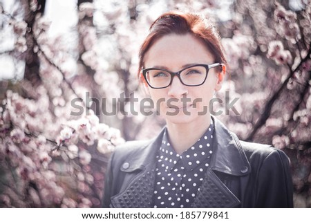 Stylized colorized vintage fashion portrait of a young sexy woman wearing glasses with beauty bokeh and small depth of field - stock photo