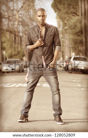 Stylized fashion portrait of a male model in urban trendy clothing in street setting with vintage retro look and feel - stock photo