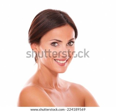 Stylized head and shoulders portrait of candid hispanic woman with brown eyes smiling at camera with nude shoulders on isolated studio - stock photo