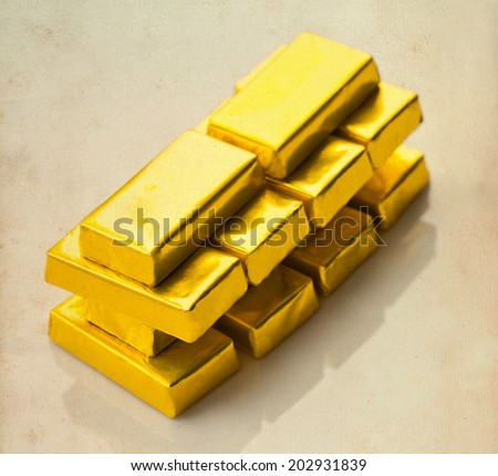 Stylized (not real) gold bars on aged paper background. Soft focus. Retro toning. - stock photo
