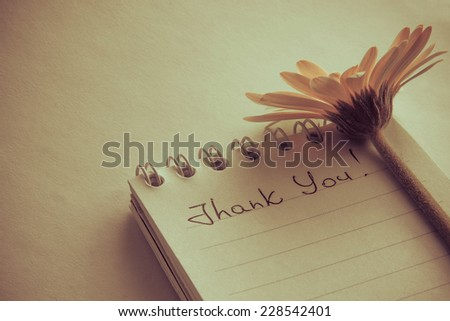 "Stylized photo of hand writting text ""Thank You"" on a white page and romantic flower - stock photo"