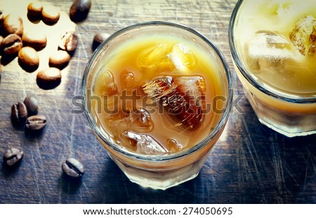 Stylized photo of iced coffee in glasses with a flecks of sunlight on a rustic wooden background - stock photo