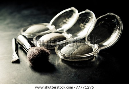 stylized photo of the different eyeshadows and make-up brushes on dark background - stock photo