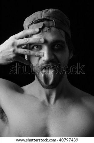 Stylized portrait of a young male model against black sticking his tongue out and making gesture