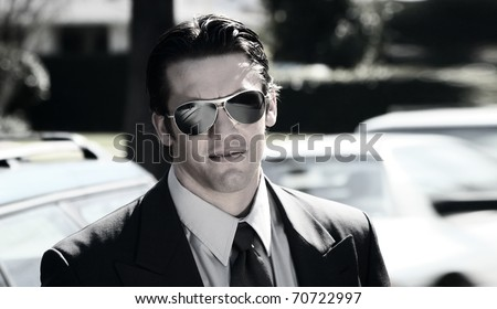 Stylized portrait of a young man in suite and sunglasses - stock photo