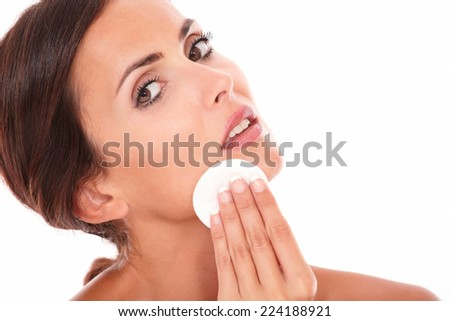 Stylized portrait of sensual and pretty woman pampering her face with cotton while looking at camera on isolated studio