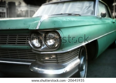 Stylized wide angle detail of an old classic green car - stock photo