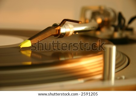 Stylus, cartridge and tonearm on a silver DJ turntable, with spinning platter, record and light
