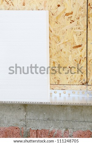 Styrofoam sheet insulation at a plywood wall - stock photo