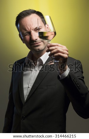 suave man tasting white wine in front of yellow background - stock photo