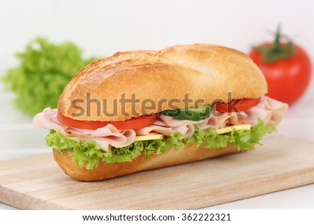 Sub deli sandwich baguette with ham, cheese, tomatoes and lettuce for breakfast