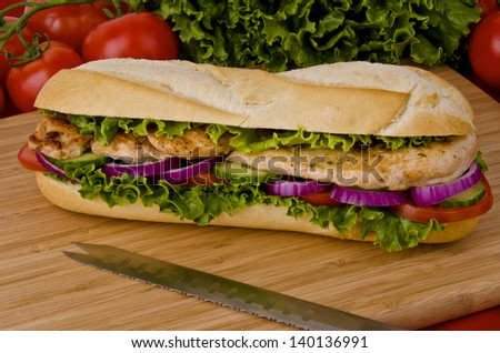 Sub sandwich on a cutting board. Tomatoes and lettuce background - stock photo