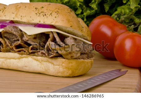 Sub sandwich on a cutting board. Tomatoes and lettuce background. - stock photo