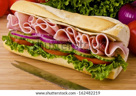 Sub sandwich on a cutting board. Tomatoes, onion and lettuce background. - stock photo