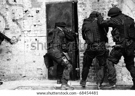 Subdivision anti-terrorist police during a black tactical exercises. Entry to the premises. Real situation. Black and white photo with film grain. - stock photo