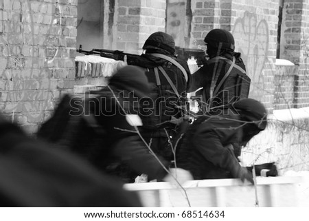 Subdivision anti-terrorist police during a black tactical exercises. Entry to the premises. Real situation. Black and white photo with film grain. SWAT