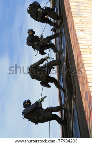 Subdivision anti-terrorist police during a black tactical exercises. Officer in full tactical gear with weapons climbing down a rope. Rope Techniques.  Real situation. - stock photo