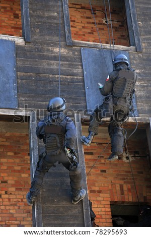 Subdivision anti-terrorist police during a black tactical exercises. Rope Techniques.  Real situation