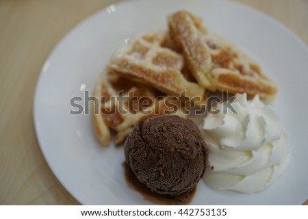 Subject is blurry and soft focus and out of focus chocolate ice cream with waffles and whipped cream on wood table background in coffee shop  - stock photo