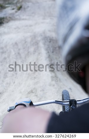 subjective view of a young man BMX biker riding his bike on a BMX session in the mountain - focus on the handlebar - stock photo