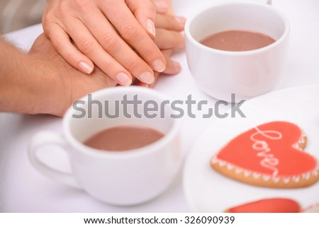 Sublime love. Close up of hands of nice loving couple holding them together on the table while drinking tea - stock photo