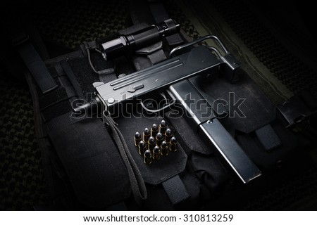 Submachine gun and 9mm round laid on a tactical vest - stock photo