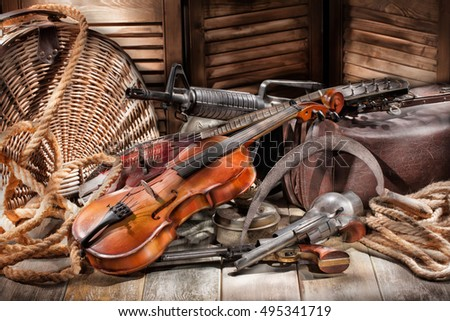Submachine gun, violin, mandoline and revolver on an old wooden desk