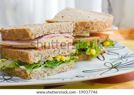 submarine sandwich with whole grain bread on wood platter - stock photo