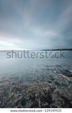 Submerged rocks in a ocean, under a cloudy sky on a bay beach on sunset. Tuscany, Italy - stock photo