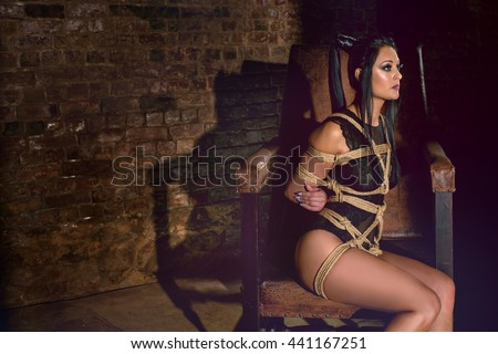 Submissive sexy kneeling woman sitting on the chair in the old room with brick wall - stock photo