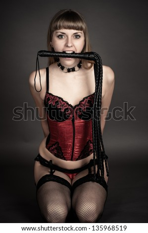 submissive woman with a whip in his mouth sitting on the floor - stock photo