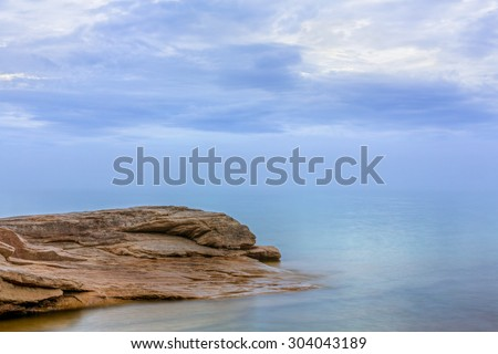 Subtle color and reflections are displayed on a cloudy, misty evening on Lake Superior along rocky Miners Beach at Upper Peninsula Michigan's Pictured Rocks National Lakeshore. - stock photo