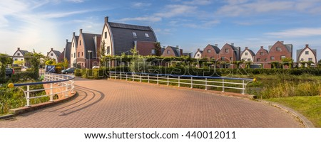Suburban area with modern family houses in a child-friendly  neighborhood with trees and gardens - stock photo