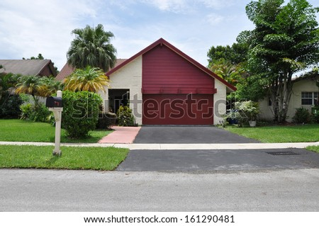 Suburban Back Split Style Home with Maroon Snout Garage Blacktop Driveway Blue Sky Clouds Residential Neighborhood USA - stock photo