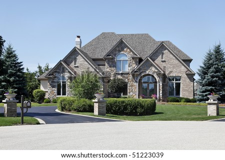 Suburban brick and stone home with cedar roof - stock photo